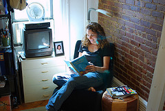 young woman reading in chair by a windwo