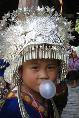 Small Asian girl in ceremonial headdress blowing bubble gum