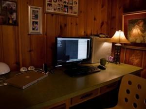 desk with computer in dark corner of room