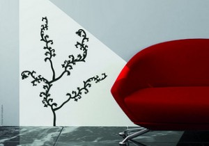 white wall with black tree outline next to modern red sofa