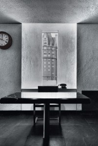 black and white photo of minimalist office with window and clock on wall