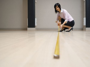 Young woman in large room, measuring floor with tape measure.