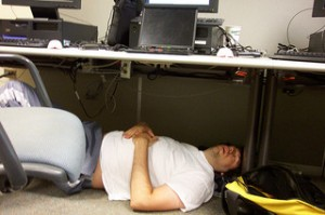 Man sleeping on the floor under a cubicle desk.