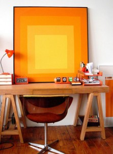 home office with mid-century modern orange chair and abstract painting