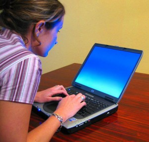 zoom computer screen, woman sitting hunched over her laptop.